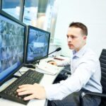 A security professional monitoring a CCTV feed.